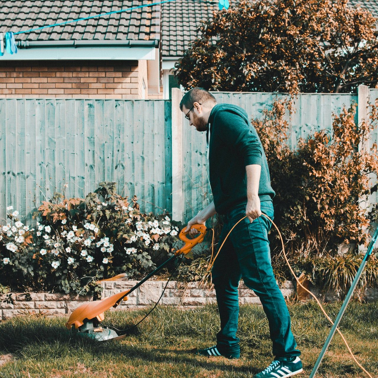man-holding-orange-electric-grass-cutter-on-lawn-1453499